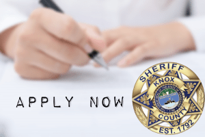 Sheriff badge in front of hands writing on paper