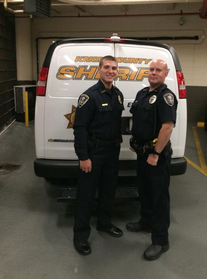 Two transport officers standing at rear of KCSO transport van
