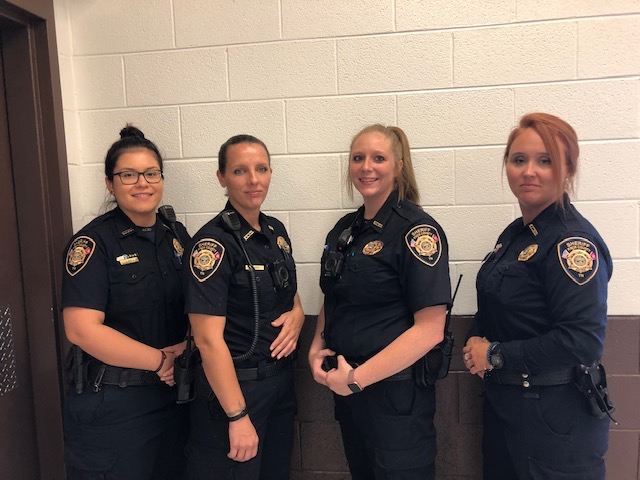 4 Female corrections officers standing next to wall