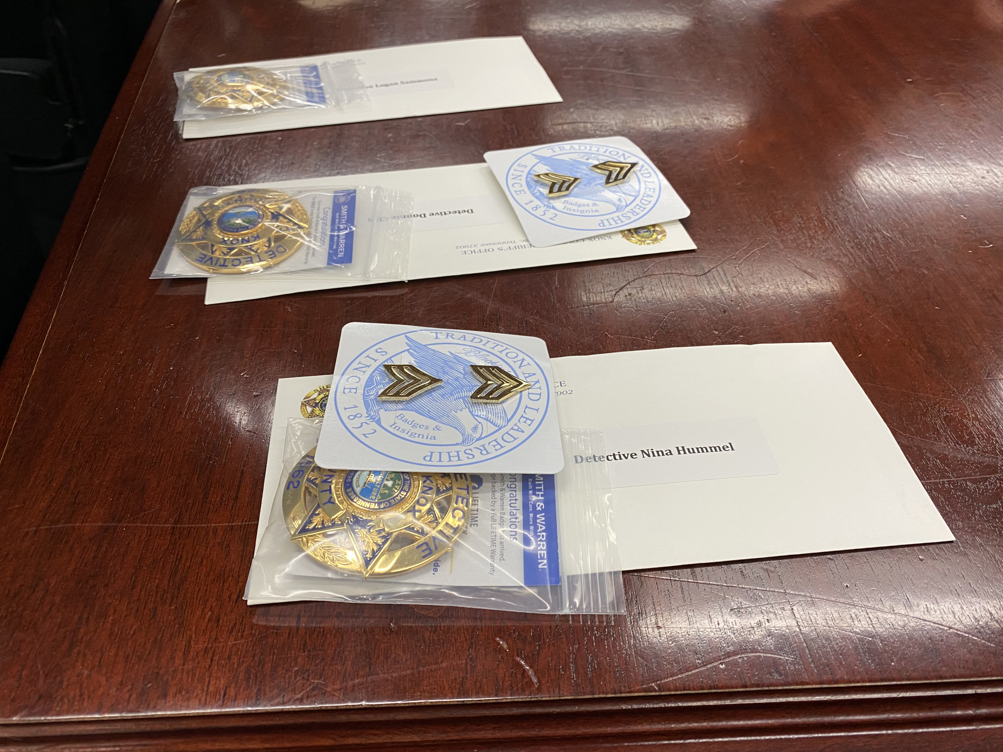 Badges, collar brass, and envelopes lying on wooden table