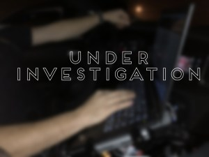 "Blurred image of officer at car computer with ""under Investigation"""