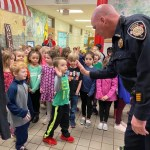 Officer high-fiving a boy as other children stand around