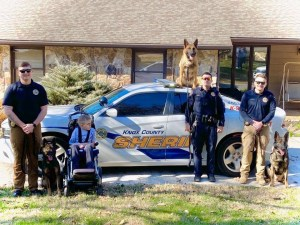 Three k9s and handlers posing with boy in wheelchair next to KCSO cruiser