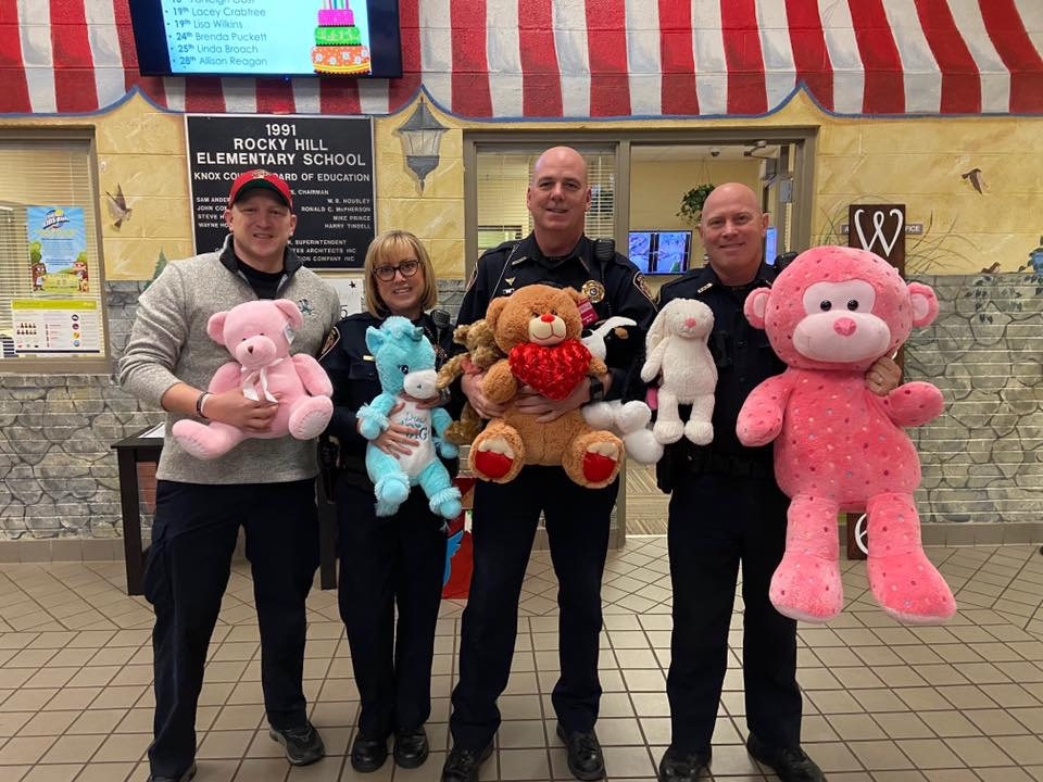 4 Officers smiling while holding stuffed animals