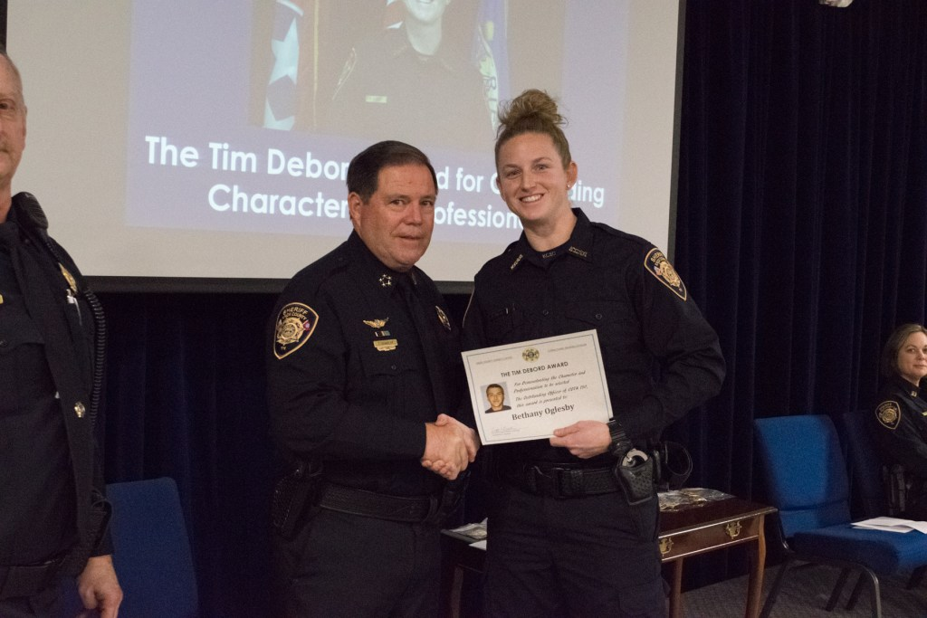 Sheriff Spangler shaking hands with female COTA graduate receiving award