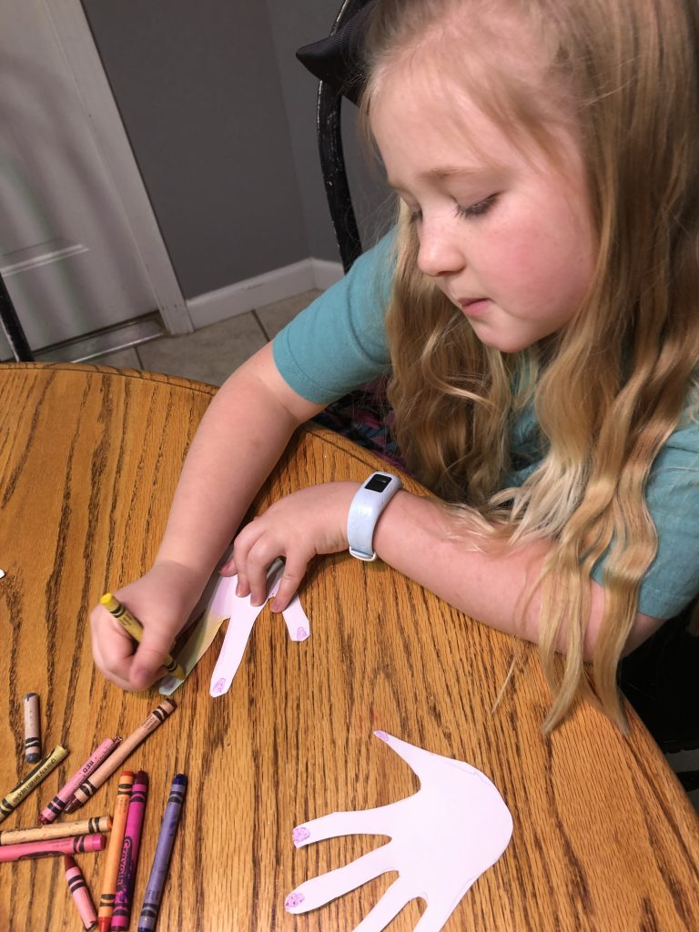 girl coloring hand cutouts