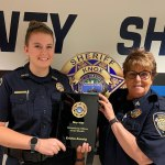 Two female KCSO deputies smiling and holding a plaque