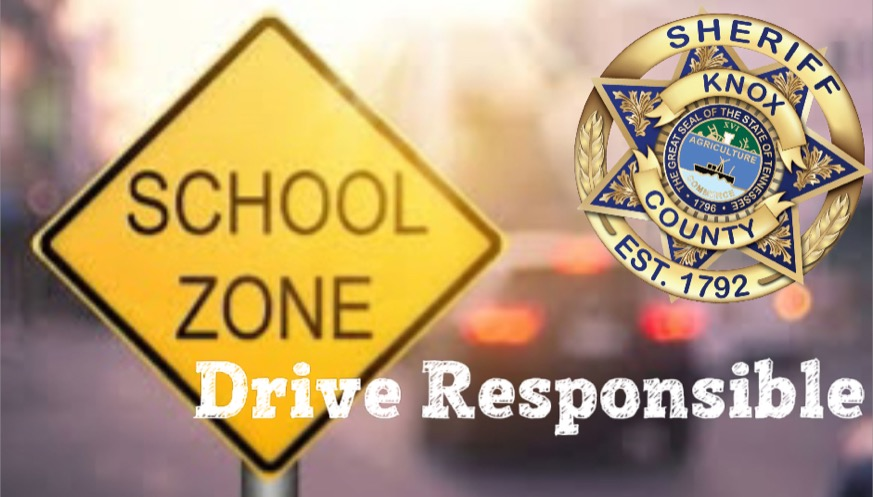 """School Zone sign with KCSO badge and """"Drive Resposibly"""" and blurred car brake lights"""