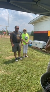 Sheriff and woman smiling at mud volleyball