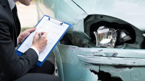 Insurance adjuster inspecting car wreck image
