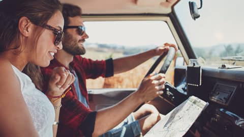 Couple driving in the sun consulting map and smiling