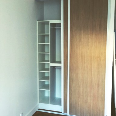 Aménagement de placards en mélaminé pour une chambre avec portes coulissantes.