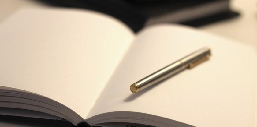 A silver pen in a blank, open journal.