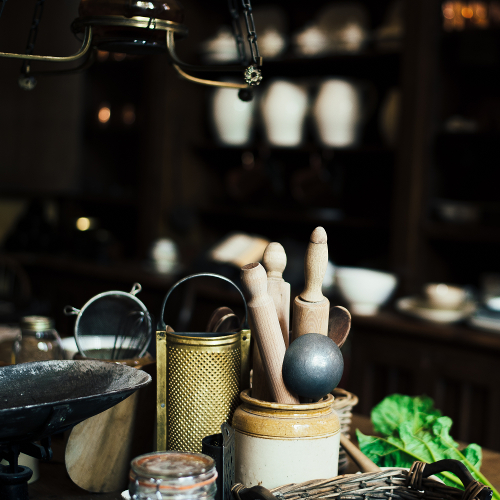 A clay jar with a metal ladle and wooden kitchen implements in an out-of-focus kitchen.