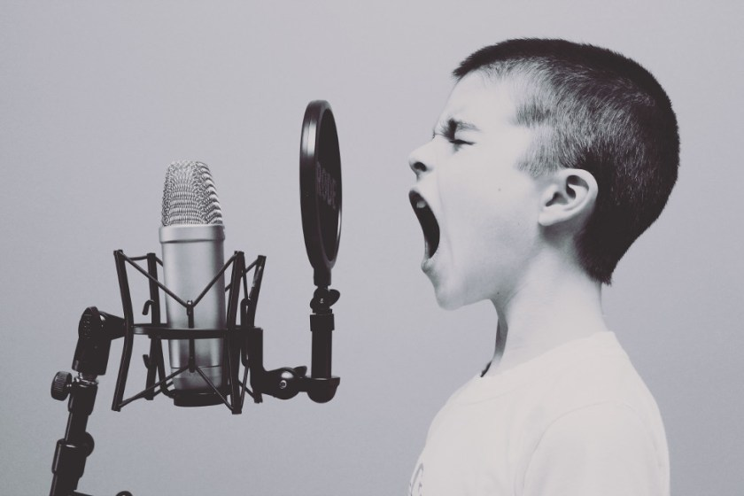 A Caucasian child with a buzz cut yelling into a complicated, professional micorphone setup.