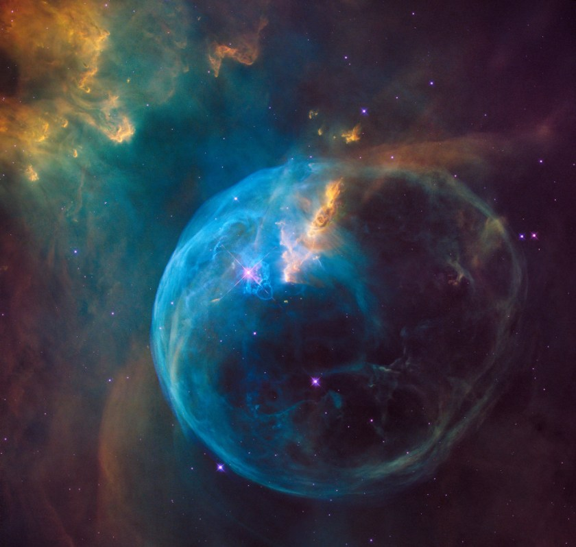 A blue spherical nebula glowing against the darkness of space.