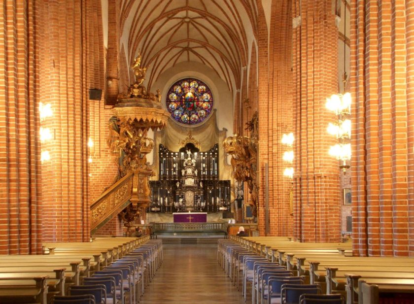 The interior of Storkyrkan in Stockholm, Sweden. The view is down the center aisle, facing a stained glass rossette. On the left hand side is a spiral staircase attached to a column, leading to a pulpit. The ceilings are high and vaulted; the columns are red brick. The seats on either side are empty.