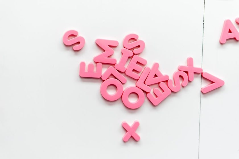 Pink magnetic plastic letters on a white background