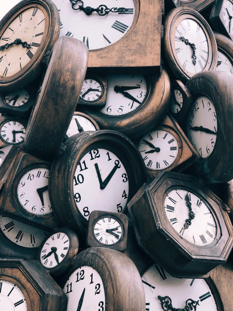 Lots of different wooden clocks, all set at different times, jumbled in a pile.