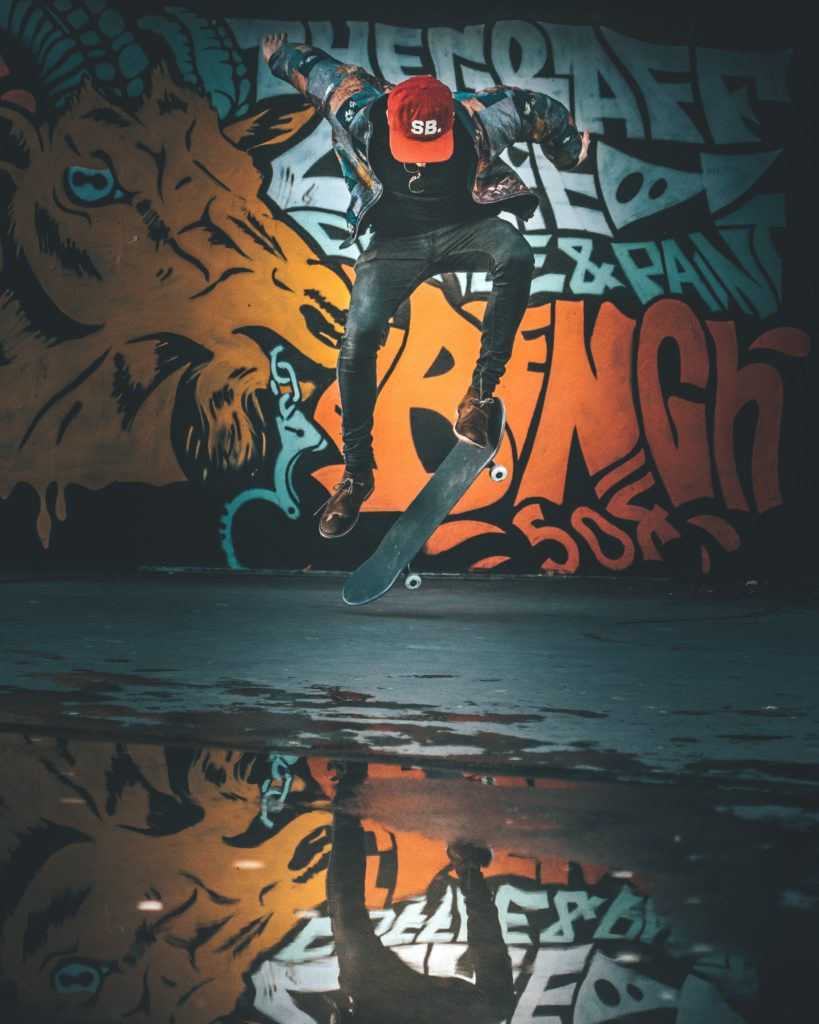 A man performing a skateboard trick in front of orange graffiti on a wall. His face is obscured by a red baseball cap and he's partially reflected in the puddle under him.