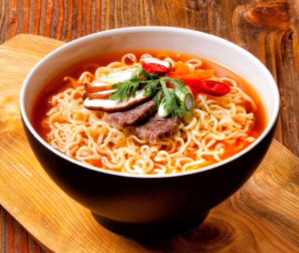 A black bowl of Shin Ramyun with beef and vegetables.