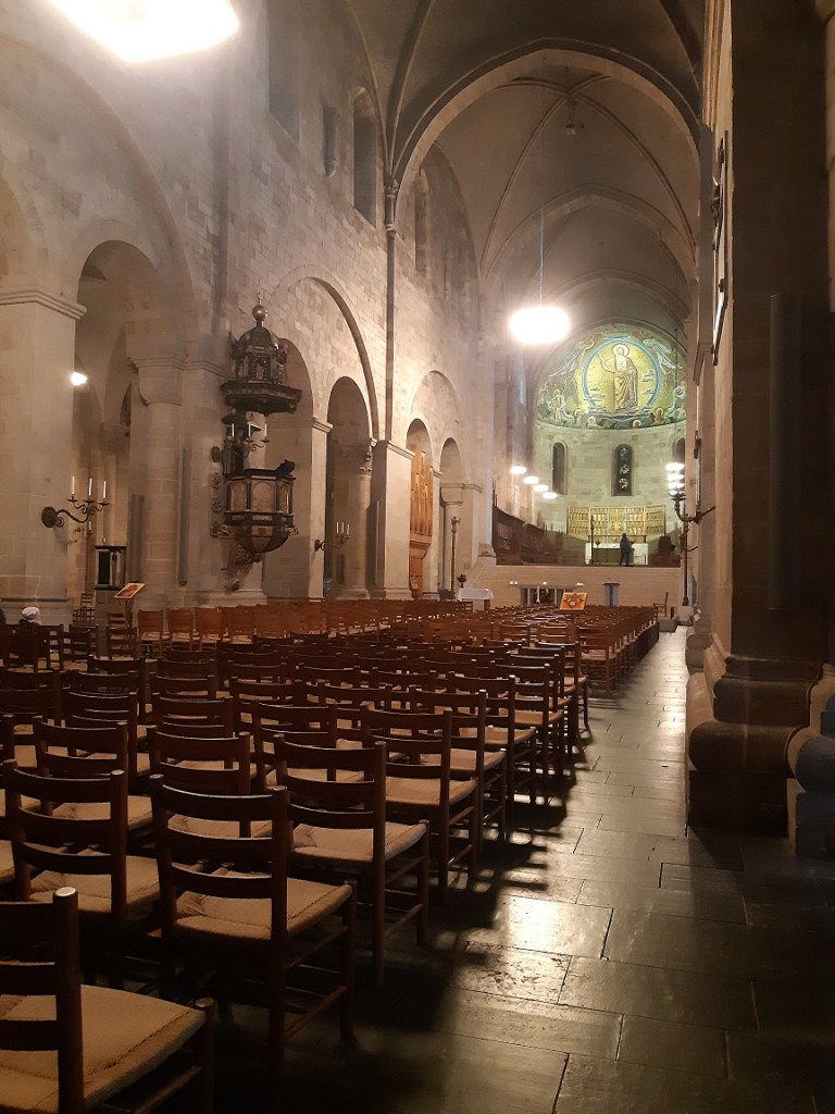 Interior of the Lund Cathedral, facing the altar behind rows of wooden chairs.