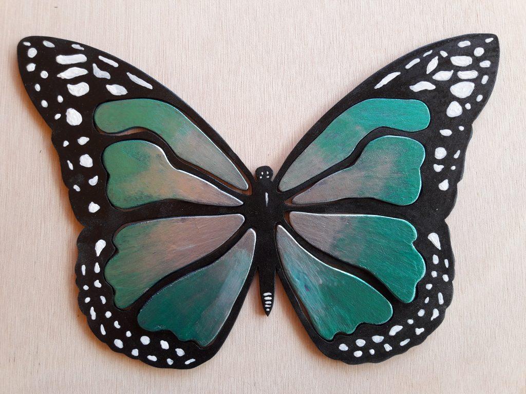 papillon en bois découpé, peint à la main avec un fond noir,couleurs des ailes,vert,argent,bleu,taches blanches en périphérie