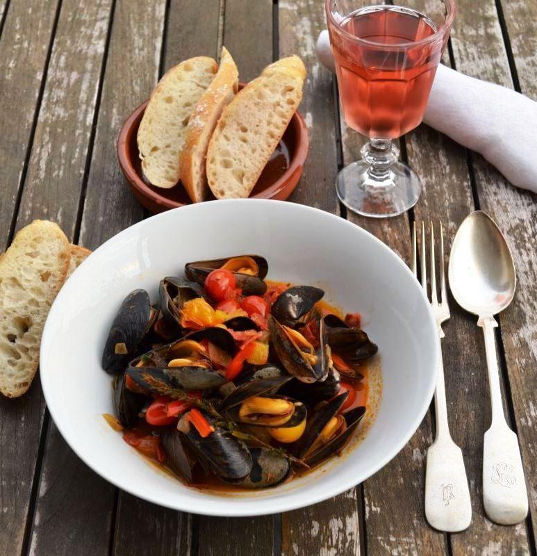 Muscheln Miesmuscheln mediterran mit Tomaten , Paprika , Wein und Baguette