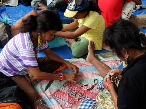 Women, men and children take part in bead-making sessions as much as they delight in wearing them.  To the right is a Manobo male wearing cascading bead earrings anchored by wooden pegs.