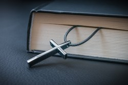 Metallic cross necklace placed between Bible pages.