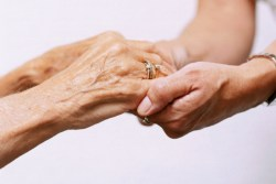 Person holding the hands of an elderly woman