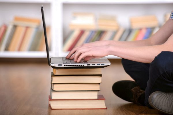 student working on a laptop on top of several books
