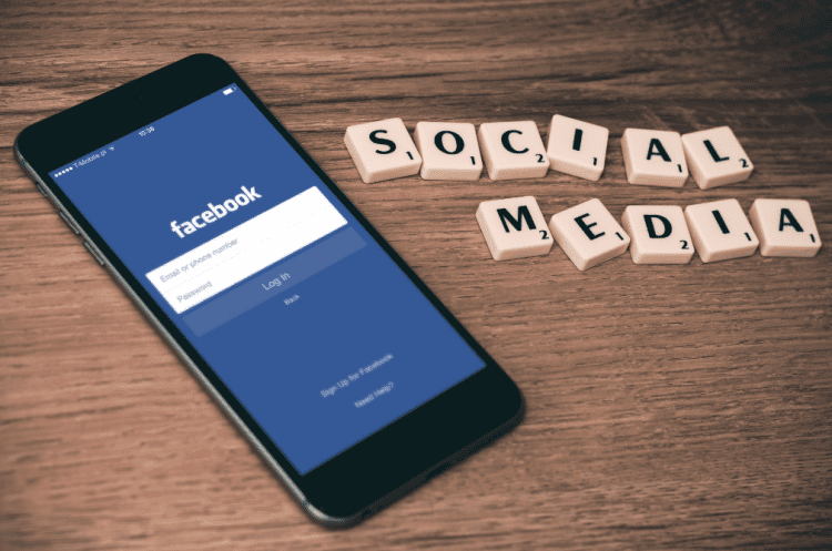 Facebook on a smartphone with the tile letters spelling social media