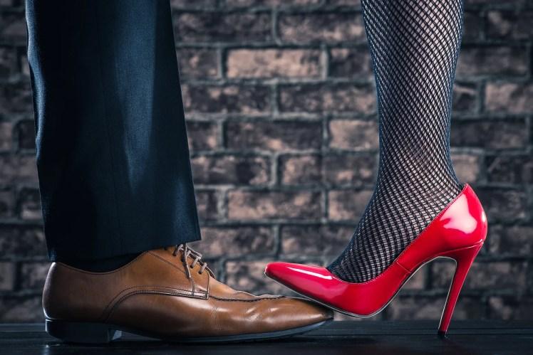 浮気性の男の足を踏みつける女性