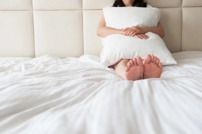 ベッドの上で枕を抱いている女性