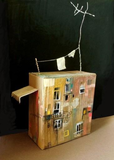 """Πέτρος Μπουλούμπασης: «Σπίτι», 2018. «Το Σπίτι ως τόπος και ως τρόπος. Ως προϊόν τέχνης και ως κατασκεύασμα, με υπόσταση διττή. Άλλοτε να δίνει """"ψυχή"""" και άλλοτε να την παίρνει από το εκάστοτε οργανικό εσωτερικό του. Να διαμορφώνει και να διαμορφώνεται. Το Σπίτι ως εσωτερική ιδιωτική εμπειρία και ως εξωτερική δημόσια προβολή. Άλλοτε καταφύγιο και φωλιά και άλλοτε αναγκαστική συνθήκη και φυλακή»."""