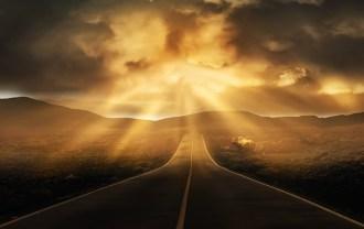雲間から差し込む光と、そこへつづく道の写真