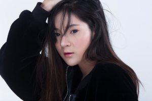 前髪をかきあげてこちらを見つめる若いアジア人女性