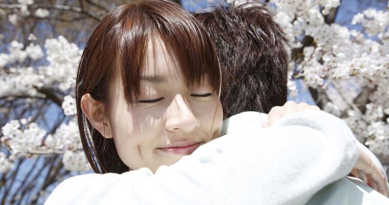 日本人女性が、どこかの国籍の人とハグしている