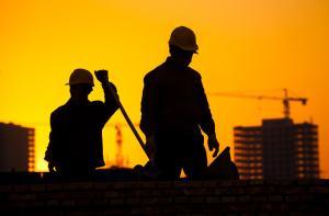 夕暮れの工事現場で作業にあたる外国人労働者たち