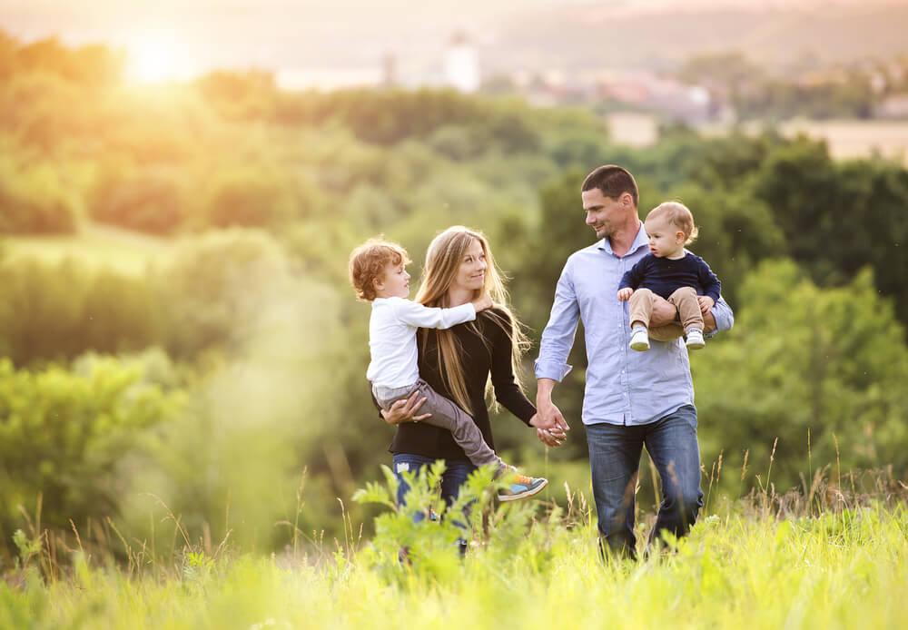草原で親子4人が手をつないで歩いている
