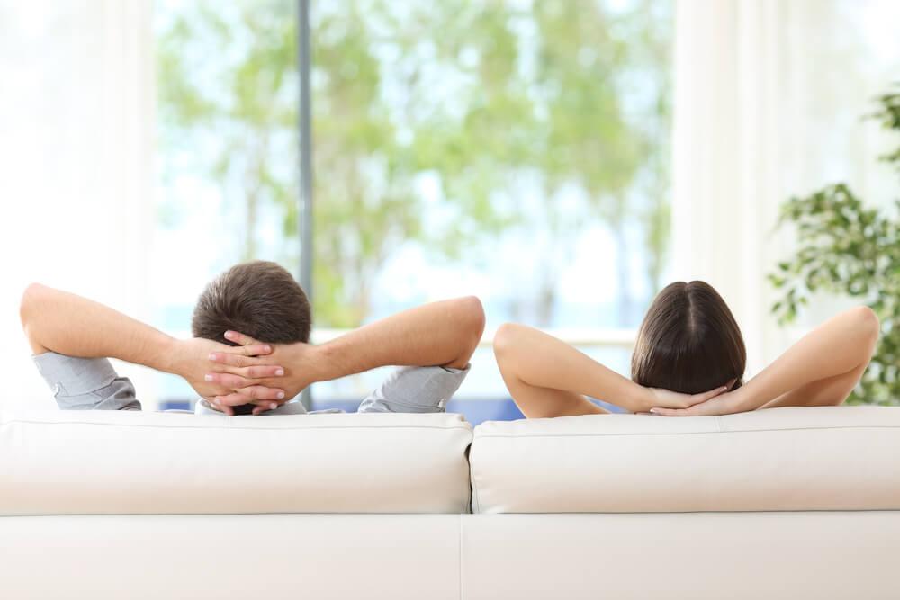 ソファに座る国際結婚カップル。お互いに目を合わさず、夫婦別姓のイメージ