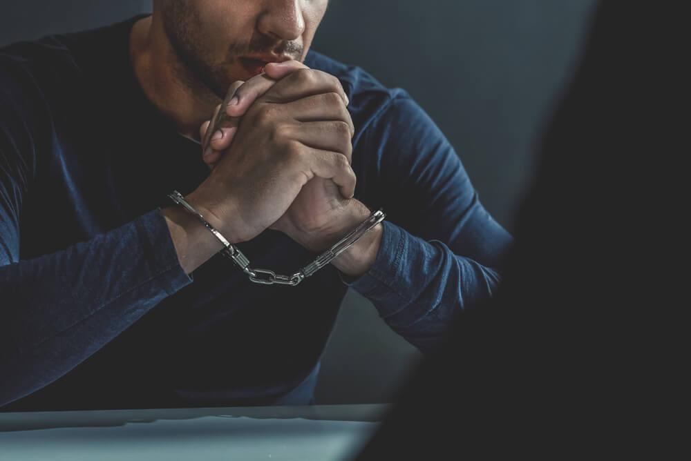 「永住権取得の要件は?」「永住ビザを取得するためには3要件必要」手錠をかけられて取り調べを受ける男性