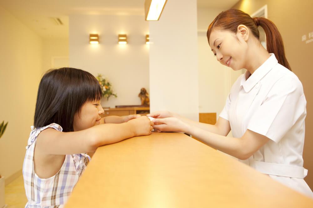 通称名が書かれた国民健康保険証を歯医者さんに提示する女の子