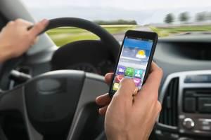 スマートフォンを操作しながら運転している、交通違反の外国人