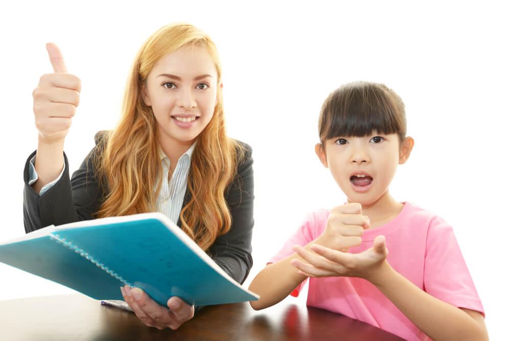 外国人英語教師が日本人女児に英語を教えている
