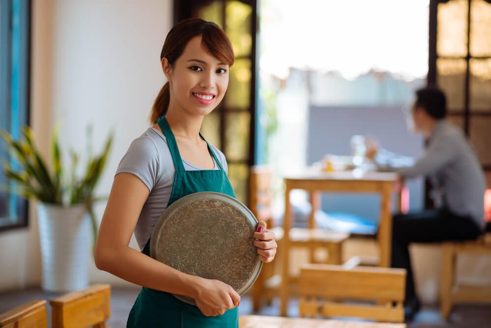 喫茶店でアルバイトをする東南アジア系の若い女性