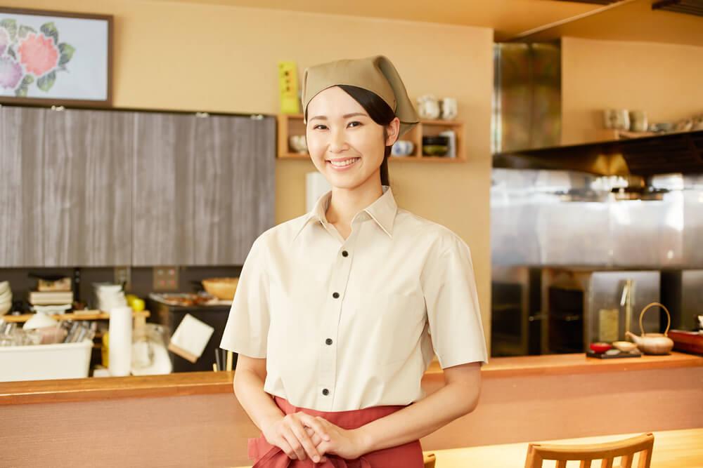 居酒屋でアルバイトをする若いアジア人女性