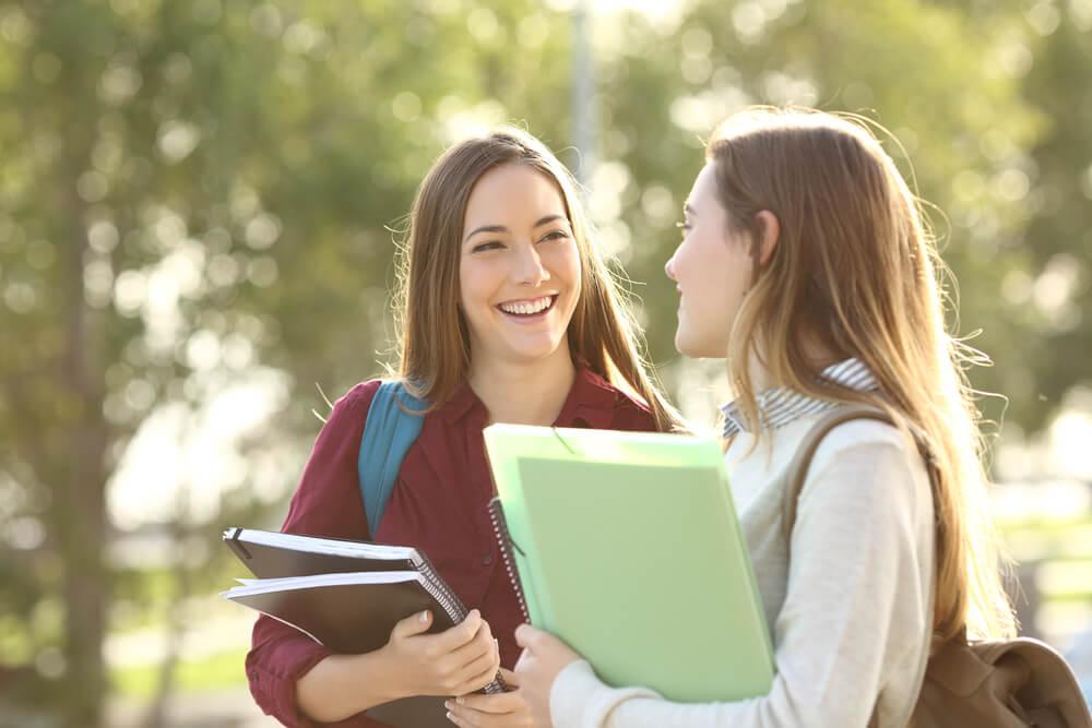 キャンパスを談笑しながら歩く、2人の欧米系の女性留学生