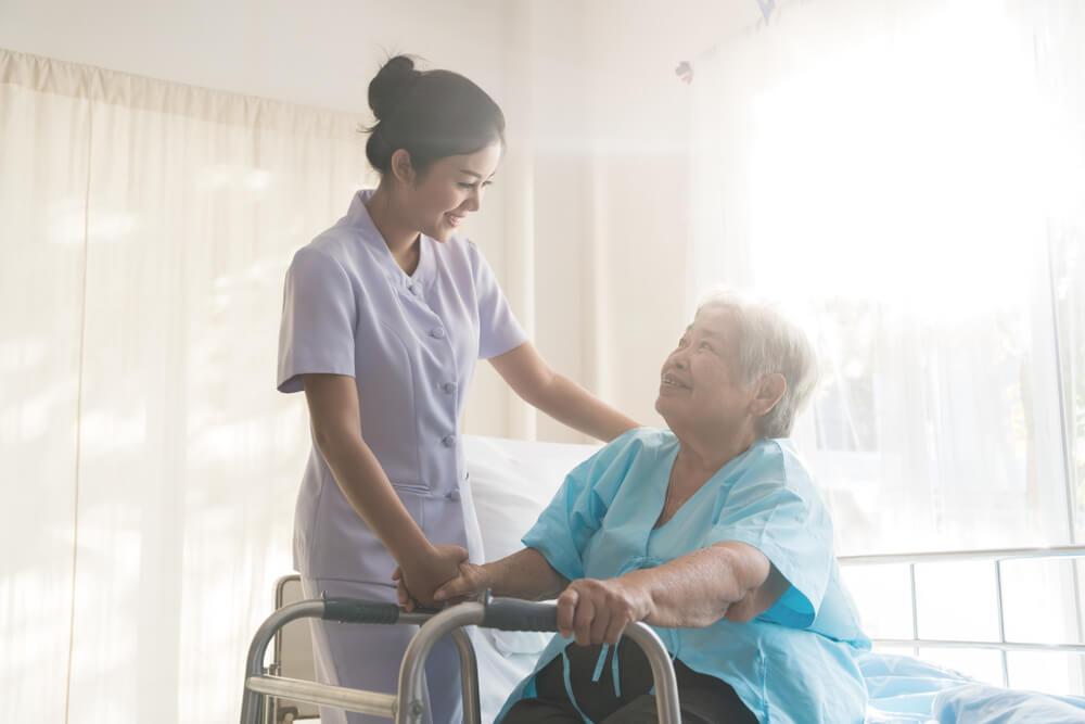 老人を介護する若いアジア人女性